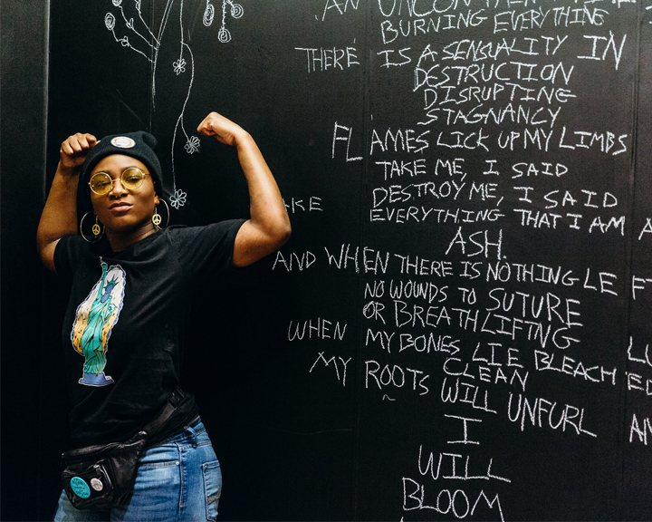 Wearing a dfrntpigeon T-shirt, NAFY alumnus Angel Carter poses in front of a mural inspired by dfrntpigeon's Transition Collection.