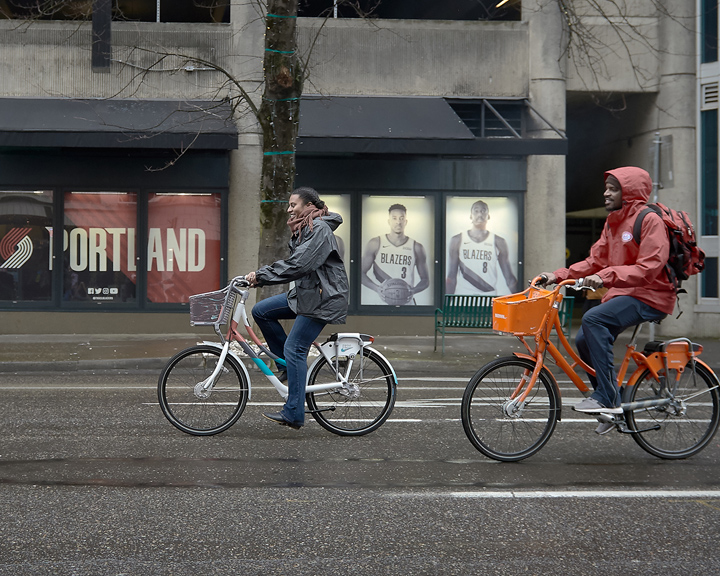 Cyclists bike through downtown Portland on bikes designed for Biketown Culture Collection