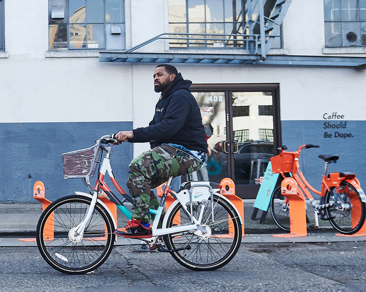 man bikes past a coffee shop on a bike designed for Biketown Culture Collection