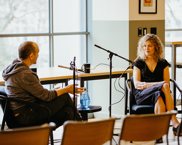 two people having a conversation while being recorded for a podcast