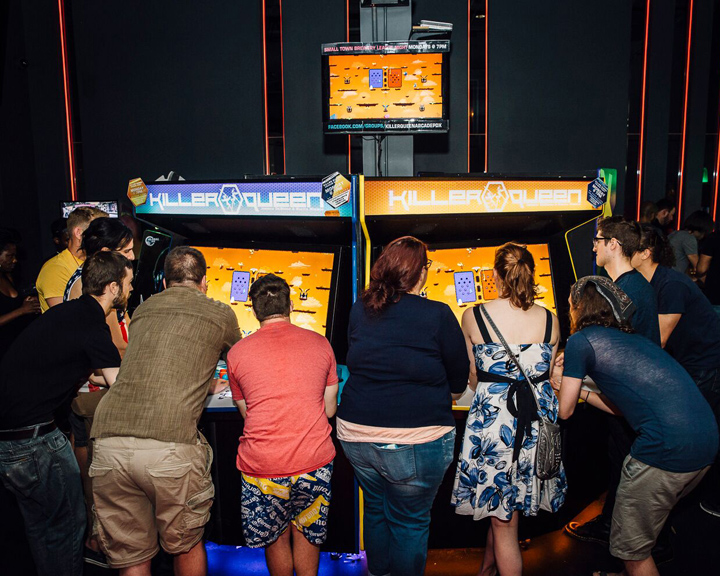 group of people surround the Killer Queen, a 10-player real-time strategy game