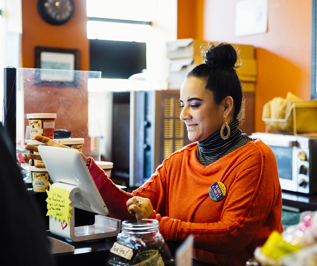 Woman at the till of a coffee house ringing up an order.